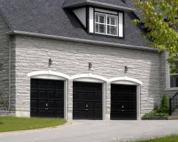 white stone brick home features three car garage with black door