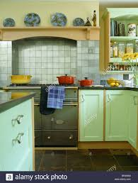 pale gray tiles on wall above green range oven in country kitchen