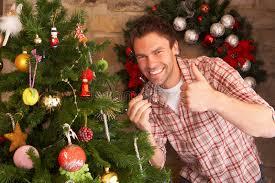 fixing christmas tree lights young man fixing christmas tree lights stock photo image of people