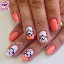 soft orange nail polish with white and black design orange nail