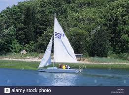 4 four people in small sailboat with sails up and life vests on