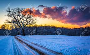 sunset trees and a snow covered field along a dirt road stock