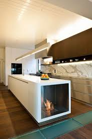 copper pendant light kitchen stone wall with fireplace red island with blue countertop wood