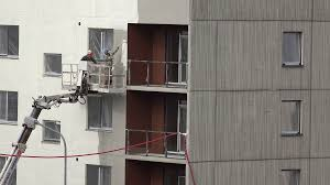 high rise man paint house wall with white paint lifted crane stock