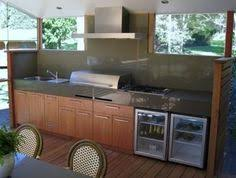 nice bbq and outdoor kitchen area enclosed by white shutters and