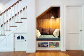 cozy reading nook under stairs in clean white contemporary next