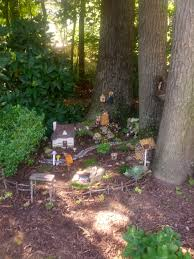 a fairy village tucked into the tree roots fairy gnome doors lead