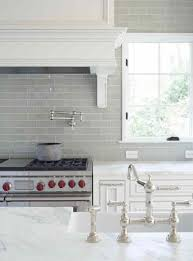 freaking out over your kitchen backsplash laurel home gray glass kitchen backsplash with carrera marble counters in a pretty traditional white kitchen nickel