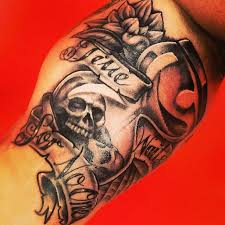 grey ink skull and banner tattoo on bicep tattooshunt com