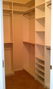 white closet with l shaped white wooden shelves and brown wooden