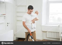 frustrated stay at home dad vacuum cleaning the carpet holding a