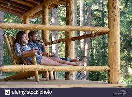 couple enjoying a glass of wine on the porch of a log cabin at the