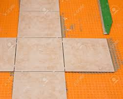 ceramic tiles laid out in a cross starter pattern for bathroom