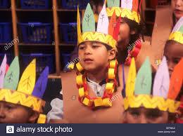 hispanic boy wears american indian costume as part of thanksgiving