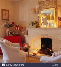 mirror on wall above mantelpiece with lighted candles in living