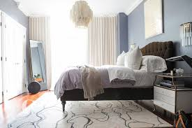 blue and brown bedroom with white capiz tiered chandelier over bed