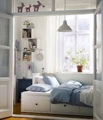 tiny bedroom bed turned sideways against wall with drawers
