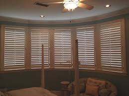 beautiful heritage plantation shutters on windows in a bedroom jpg