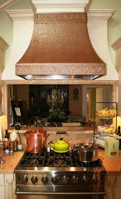 custom bronze range hood with hand forged steel detailing love