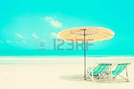 blue sea and white sand beach with beach chairs and parasol at