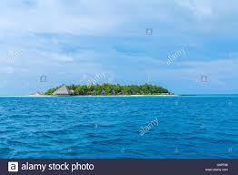 small atoll island with traditional wooden bungalows and indian