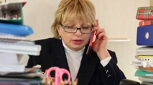 chief accountant senior woman chief accountant in glasses and with red smartphone