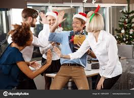 colleagues celebrating christmas party in office smiling giving