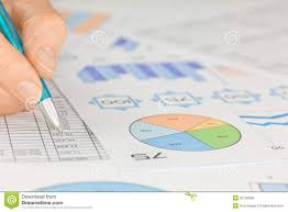 Graph Spreadsheet Hand With Pen Working On Spreadsheet And Graphs Royalty Free Stock