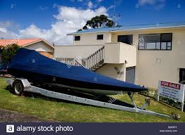 covered dinghy in front of a modern house for sale new zealand