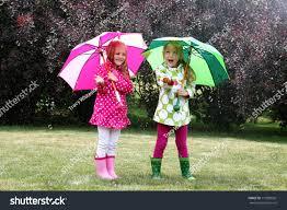 twin young girls playing rain coats stock photo 110905361