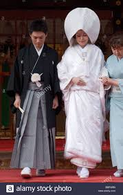 bride and groom wearing traditional kimono leaving shinto shrine