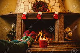 feet in woollen socks by the christmas fireplace woman relaxes
