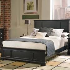 black wooden bed frame with headboard and white bedding set on the
