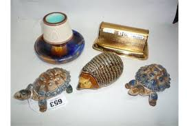 a wedgwood majolica match striker three wade ornaments and a desk