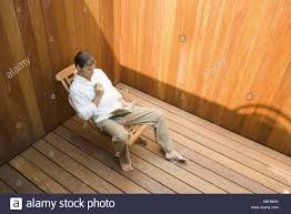 High Sitting Chair Man Sitting In Lounge Chair Reading Book Apple In Hand High