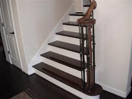 stained oak stairs and white painted risers and dark wood flooring