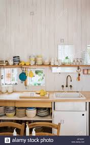 kitchenware on shelf above sink set in wooden worktop in country