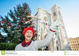 woman pointing on something near christmas tree in florence stock