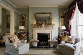 Wide Armchairs Wide Armchairs In Front Of English Fireplace With Ornaments On