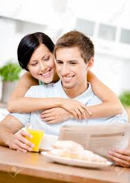 le journal de la femme cuisine femme embrasse copain manger qui est assis à la table de cuisine