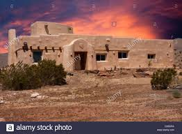 adobe house adobe house in nevada desert with dramatic sunset stock photo