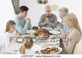 picture of family saying grace at thanksgiving table u12721877