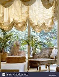 cream festoon blinds on french windows above chaiselongue in