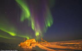 awe rora borealis green and purple light dances across the