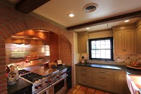 copper backsplash black marble countertop slide in range and vent