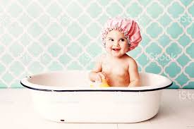 baby shower caps baby in pink shower cap plays with a rubber duck in the bath stock