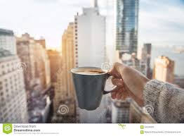 man holding coffee cup in luxury penthouse apartments with view to
