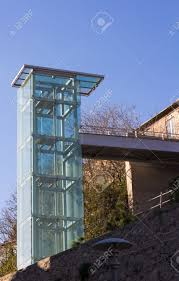 a modern outdoor glass elevator with a bridge in front of a bright