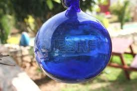 a decorative blue glass hanging in the garden on a