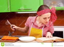 femme en cuisine femme dans la cuisine avec le livre de recette de couteau photo